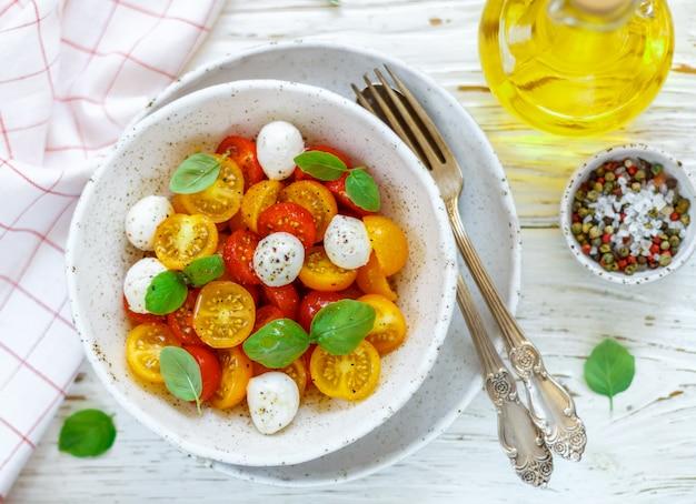 Köstlicher salat von gelben und roten kirschtomaten, mozzarella, basilikum, gewürze. caprese Premium Fotos