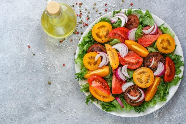 Köstlicher sommersalat aus bunten tomaten, roten zwiebeln und salat mit gewürzen Premium Fotos