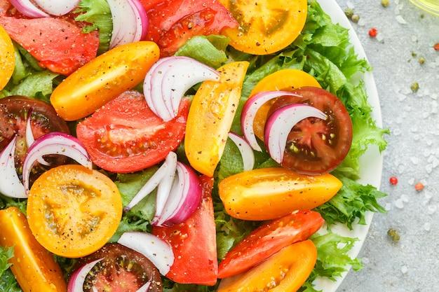 Köstlicher sommersalat von bunten (gelben, roten und schwarzen) reifen tomaten Premium Fotos