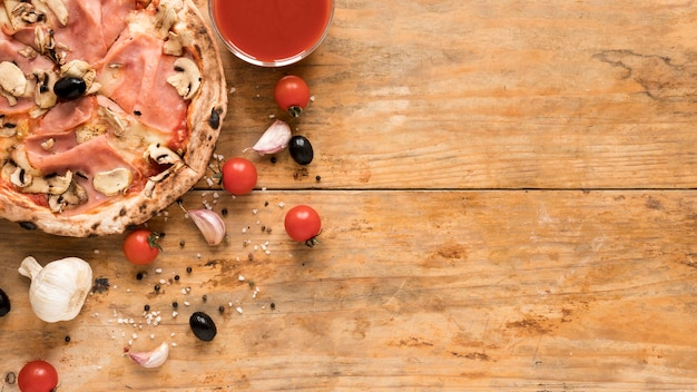 Köstlicher speck; pilzpizza in der nähe von knoblauch; kirschtomate; schwarze olive und schüssel tomatensauce über schreibtisch aus holz Kostenlose Fotos