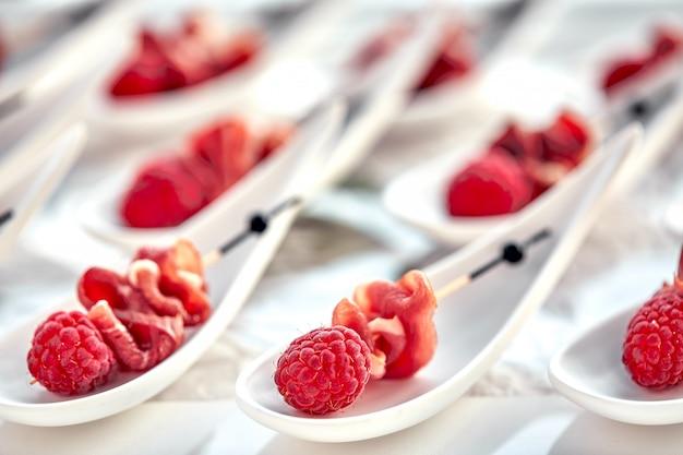Köstliches canapes hamon mit himbeeren. konzept von essen, restaurant, catering, menü. Premium Fotos