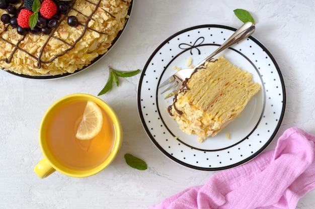 Köstliches festliches schichtdessert mit blätterteig und pudding, dekoriert mit frischen beeren und einer tasse zitronentee Premium Fotos