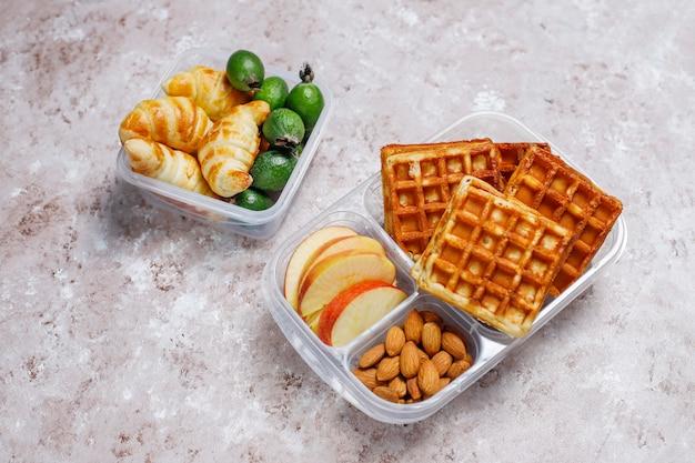 Köstliches frühstück mit mandeln, scheiben der roten äpfel, waffeln, hörnchen auf plastikbrotdose auf licht Kostenlose Fotos