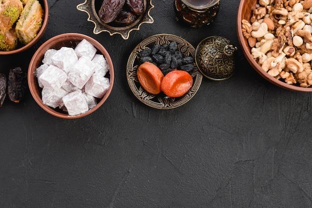 Köstliches lukum; trockenfrüchte und nüsse auf schwarzem strukturiertem hintergrund Kostenlose Fotos