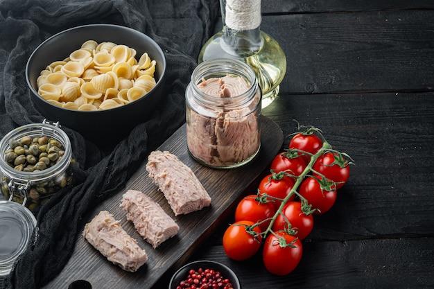 Köstliches lumaconi-nudelgericht mit thunfisch und babykapern auf schwarzem holztisch Premium Fotos