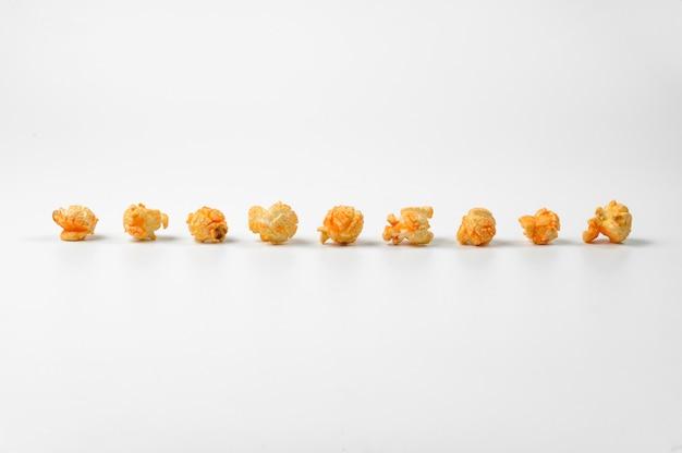 Köstliches popcorn in einer linie auf weiß Premium Fotos