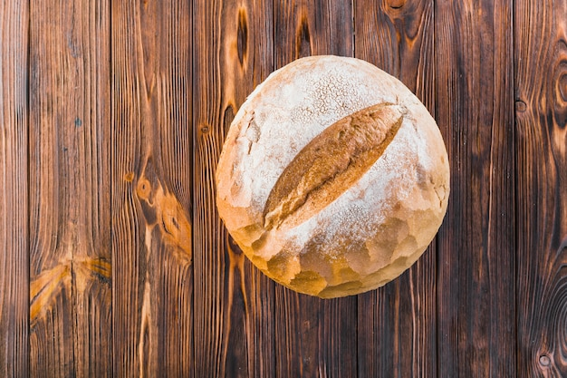Köstliches vollständiges rundes brot auf hölzernem hintergrund Kostenlose Fotos