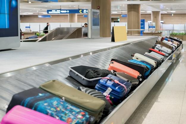 Koffer oder gepäck mit förderband im flughafen. Premium Fotos