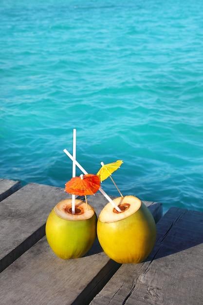Kokosnuss coktails in karibischen meeren auf hölzernem pier Premium Fotos