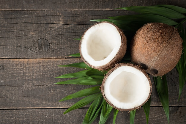 Kokosnuss mit grün verlässt auf einem hölzernen hintergrund. Premium Fotos
