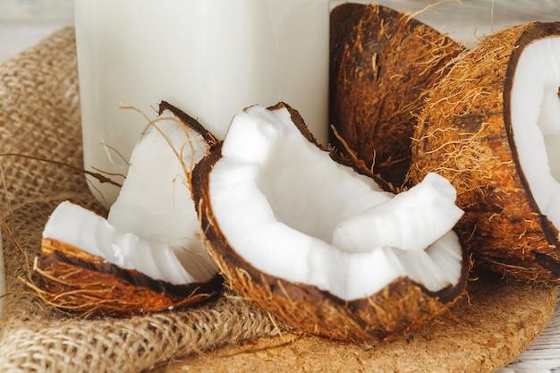 Kokosnuss und kokosmilch auf rustikalem holztisch Premium Fotos