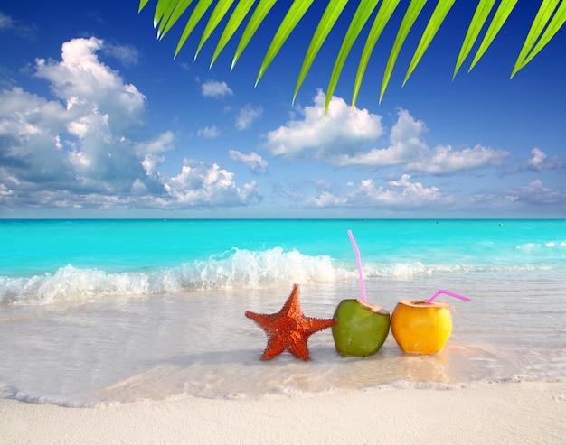 Kokosnusscocktailsaft und -starfish im tropischen strand Premium Fotos