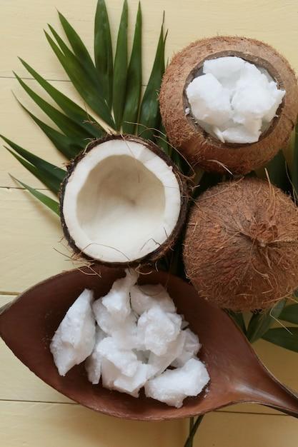 Kokosnussöl. große stücke kokosöl in einer kokosnussschale, kokosnussnüsse auf gelbem holzbrett. bio bio kokosöl Premium Fotos
