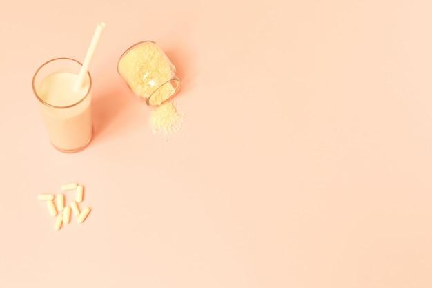 Kollagenpulver, milch und pillen auf rosa hintergrund. Premium Fotos