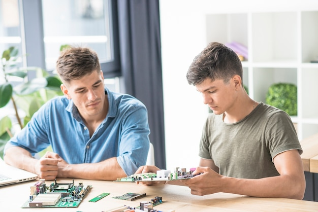 Kollege, der den it-ingenieur repariert pc-motherboard betrachtet Kostenlose Fotos