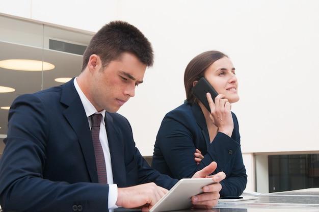 Kollegen, die tablette verwenden und draußen um telefon am schreibtisch ersuchen Kostenlose Fotos