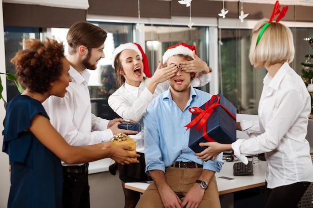 Kollegen feiern weihnachtsfeier im büro lächelnd geschenke geben. Kostenlose Fotos