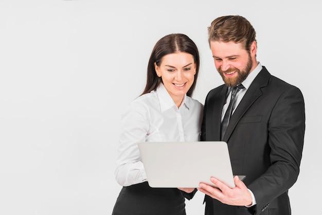 Kollegen männlich und weiblich lächelnd und laptop zu betrachten Kostenlose Fotos