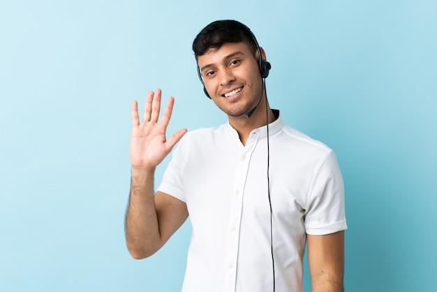 Kolumbianer des telemarketers, der mit einem headset über isoliertem gruß mit hand mit glücklichem ausdruck arbeitet Premium Fotos
