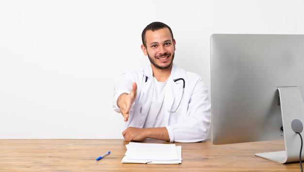 Kolumbianischer mann doktors, der hände für das schließen viel rüttelt Premium Fotos