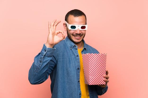Kolumbianischer mann mit den popcorns, die ein okayzeichen mit den fingern zeigen Premium Fotos