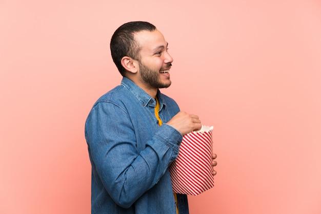 Kolumbianischer mann mit popcorn über getrenntem rosa Premium Fotos