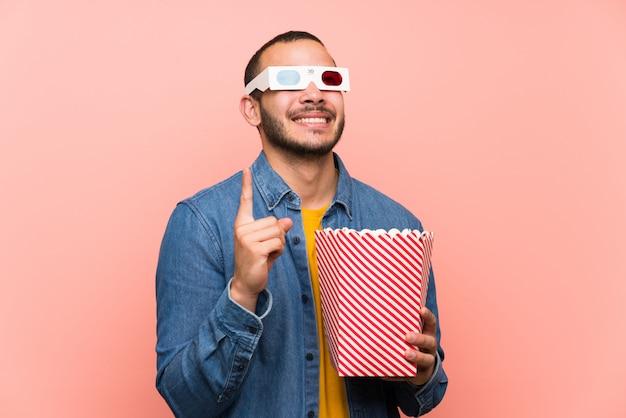 Kolumbianischer mann mit popcorn zeigt mit dem zeigefinger eine großartige idee Premium Fotos