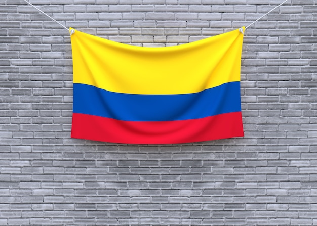 Kolumbien-flagge, die an der backsteinmauer hängt Premium Fotos