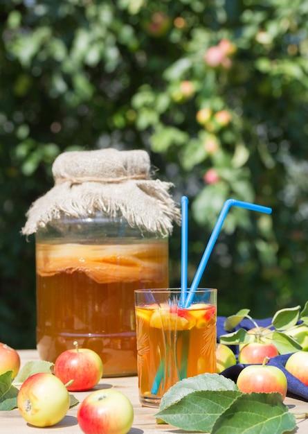 Kombucha-getränk in einem glas und einem glas mit zwei strohhalmen, fermentierten äpfeln, auf einem holztisch. rustikaler stil. Premium Fotos