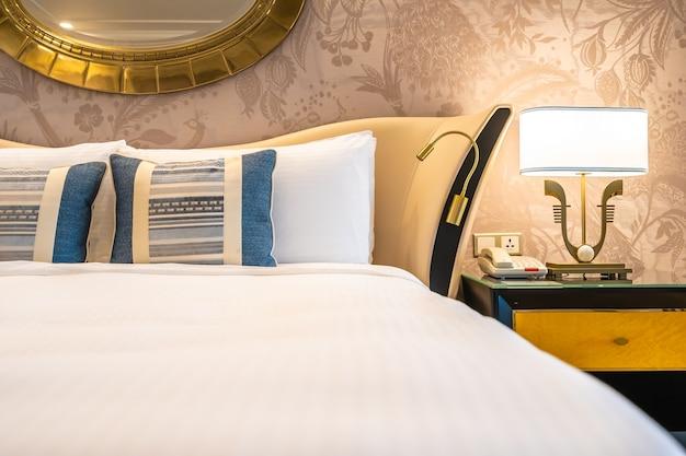 Komfortable kissen auf dem bett mit licht lampe dekoration Premium Fotos