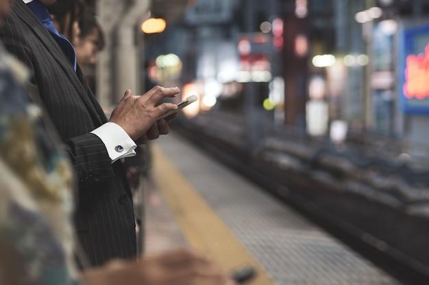 Kommunikation. leute, die handy während auf plattform verwenden Premium Fotos