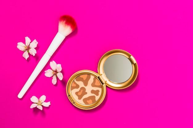 Kompakte pulverpalette mit make-upbürste und -blumen auf rosa hintergrund Kostenlose Fotos