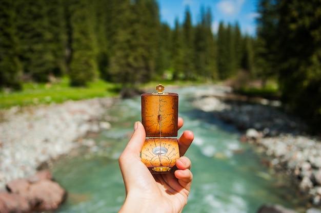 Kompass in den händen auf hintergrund ein gebirgsfluss Premium Fotos