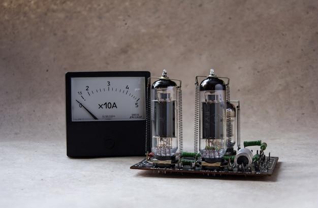 Komposition aus röhrenverstärker und vintage amperemeter. Premium Fotos