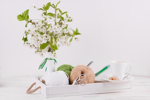 Komposition mit einer vase und einem holztablett und garnknäuel für handarbeiten. Premium Fotos