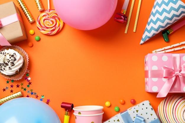 Komposition mit geschenkboxen und b-day-accessoires auf orangefarbenem hintergrund, platz für text Premium Fotos