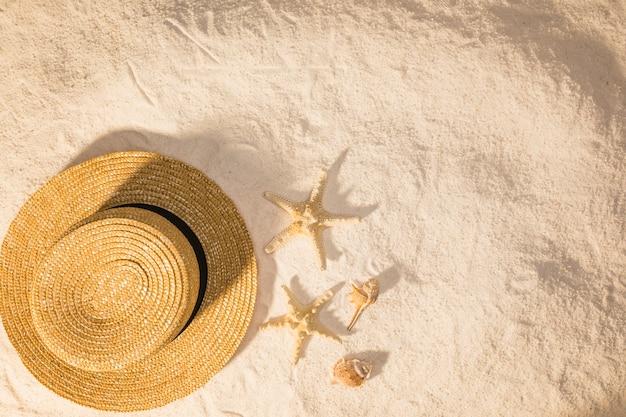 Komposition mit sommeraccessoire und seestern auf sand Kostenlose Fotos