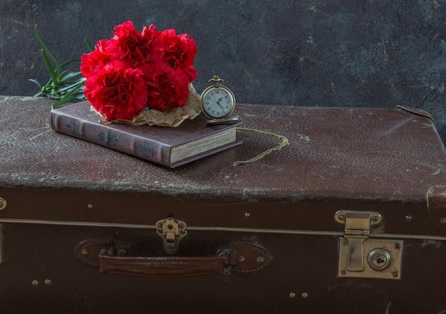 Komposition über erinnerungen: die zeit des krieges, auf einen koffer, uhren, nelken und ein buch Premium Fotos