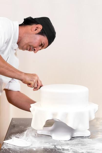 Konditor, der eine hochzeitstorte mit weißem fondant verziert. Premium Fotos