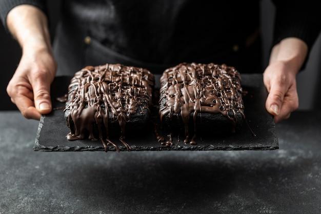 Konditor, der zwei schokoladenkuchen hält Kostenlose Fotos