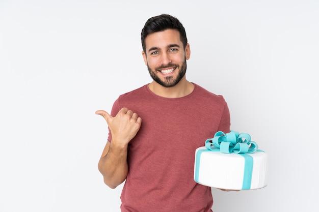Konditor mit einem großen kuchen auf weiß, der zur seite zeigt, um ein produkt zu präsentieren Premium Fotos