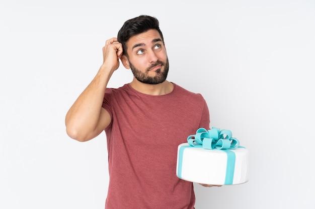 Konditor mit einem großen kuchen auf weiß, der zweifel hat und mit verwirrendem gesichtsausdruck Premium Fotos