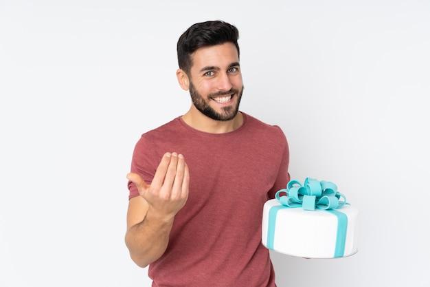 Konditor mit einem großen kuchen auf weißer wand, der einlädt, mit der hand zu kommen. Premium Fotos