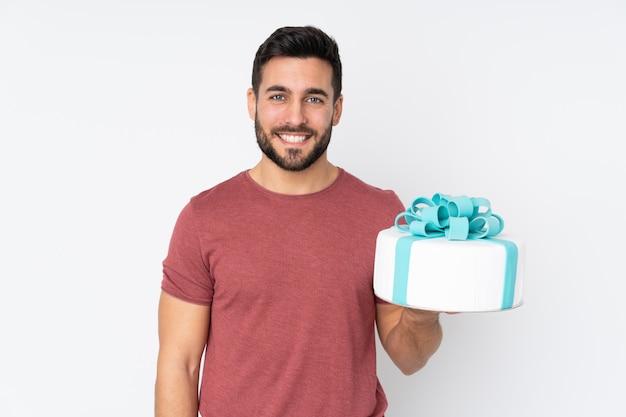 Konditor mit einem großen kuchen auf weißer wand, der viel lächelt Premium Fotos