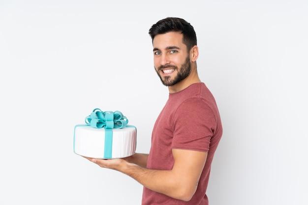 Konditor mit einem großen kuchen auf weißer wand Premium Fotos