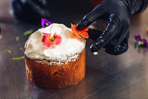 Konditor schmückt osterkuchen mit zarten blumen. Premium Fotos