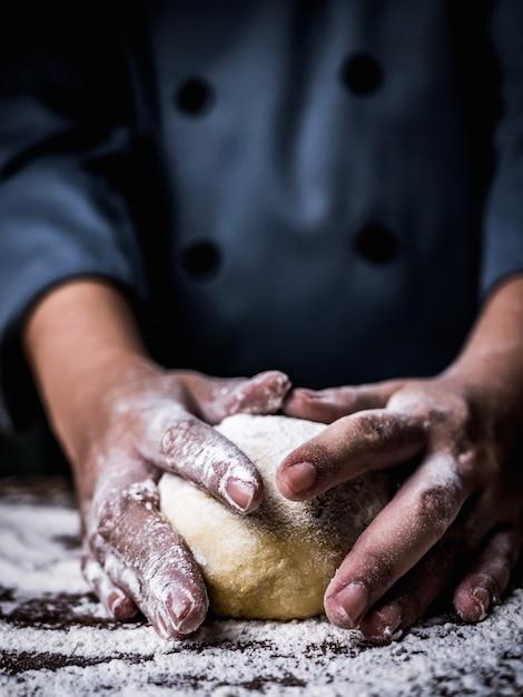 Konditorhand, die rohen teig mit dem besprühen des weißmehls über küchentisch knetet. Premium Fotos