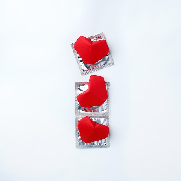Kondome und rote herzen auf weißem hintergrund. liebe konzept. valentinstag, romantikveranstaltung Premium Fotos