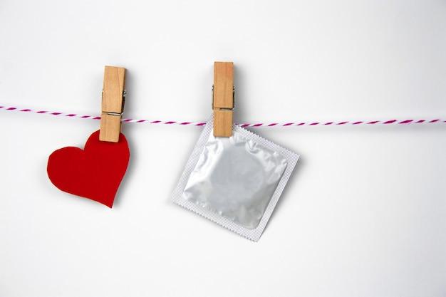 Kondomsatz vom kleidungsstift von einem weißen hintergrund Premium Fotos