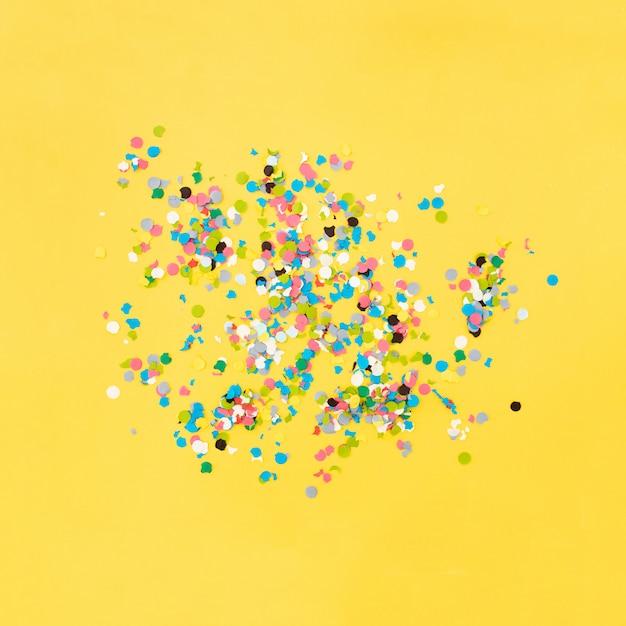 Konfetti auf gelbem grund nach der party Kostenlose Fotos